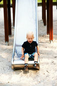 Young boy having fun on a slide — Stock Photo