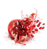 Falling and crack pomegranate with splashes of juice and seeds — Stock Photo