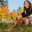 Young woman relaxing in the autumn park — Stock Photo