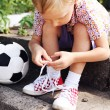 Boy trying to tie lace on his sneakers — Stock Photo #14545519