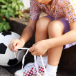 Stock Photo: Boy trying to tie lace on his boots