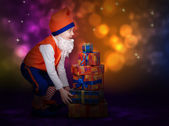 Surprised little gnome with gift boxes — Stock Photo