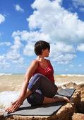 Kvinna i halv spinal twist yogaställning — Stockfoto
