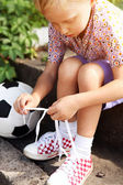 Boy trying to tie lace on his boots — Stock Photo