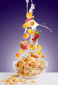 Falling gold corn flakes and strawberry with splash of milk — Stockfoto