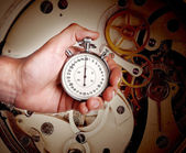 Men's hand with timer on the background of watch mechanism — ストック写真
