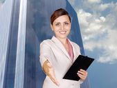 Smiling business woman with hand outstretched for a handshake — Stock Photo
