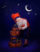 Funny little gnome with christmas gift at the night — Stock Photo