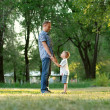 Father and son standing on the park lawn — Stockfoto