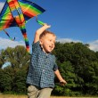 Running boy with kite in rainbow colors — Stock Photo
