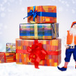 Little christmas elf with big gift boxes — Stock Photo