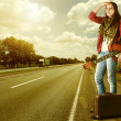 Yong Girl  with guitare and old suitcase at the highway — Stock Photo