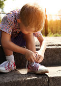 Boy tying the laces on sneakers himself — Stockfoto