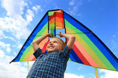 Boy with bright kite over the head — Stock Photo