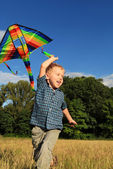 Running boy with kite in rainbow colors — Stok fotoğraf