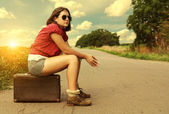 Auto stop traveller sitting on suitcase at the road — Stock Photo