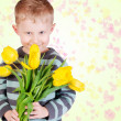 Cute little boy with yellow tulips — Stock Photo