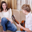 Teenage boy playing on guitar for his girlfriend 1 - Stock Photo