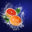 Stock Photo: Grapefruits wuith leaves in water splahes