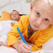 Royalty-Free Stock Photo: Little son drawing into the bed