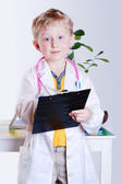 Smiling little boy in doctor's uniform — Stock Photo