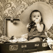 Stock Photo: Baby girl sitting into old suitcase