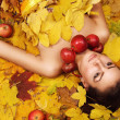 Beautiful girl lying over yellow leaves carpet — Stock Photo