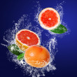 Stock Photo: Juicy grapefruit in water splahes
