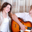 Two teenagers - boy and girl singing together by guitar — Stock Photo