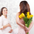 Little daughter has a flowers for her pregnant mother — Stock Photo