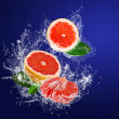 Stock Photo: Segments of grapefruits with leaves in water splashes