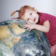 Stock Photo: Little girl gently hugs the Earth globe