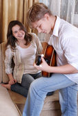 Teenage boy playing on guitar for his girlfriend — Fotografia Stock