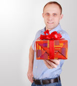 Handsome young man with gift box — Stock Photo