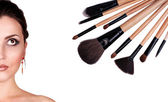 Woman portrait with makeup brushes — Stock Photo