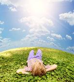 Lying on green grass carefree boy — Stock Photo