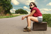 Yong girl traveler on the lonely road — Stock Photo