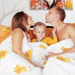 Smiling family with little boy child play piddle in bed — Stock Photo