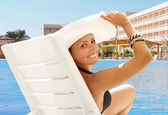 Donna sorridente felice nel cappello bianco vicino alla piscina — Foto Stock