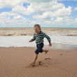 Stock Photo: Happy little boy running at the sea coast