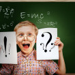 Emotional screaming pupil boy near chalkboard - Stok fotoğraf