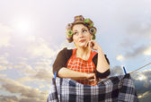 Beautiful housewife hanging clothes — Stock Photo