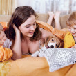 Children playing with puppy in bed - Stok fotoraf