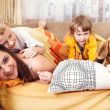 Happy children plaing with puppy in bed — Stock Photo #24083669