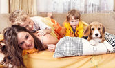 Happy children plaing with puppy in bed — Stock Photo