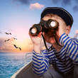Sailor boy with binoculars in the boat - Stock Photo