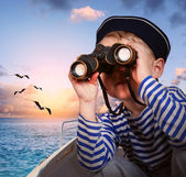 Sailor boy with binoculars in the boat — Stok fotoğraf