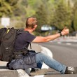 Hitchhiker man traveler sitting on the roadside - Stock Photo