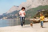 Spelen en gelukkige familie met hond — Stockfoto