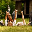 Four friends lying in grass — Stock Photo